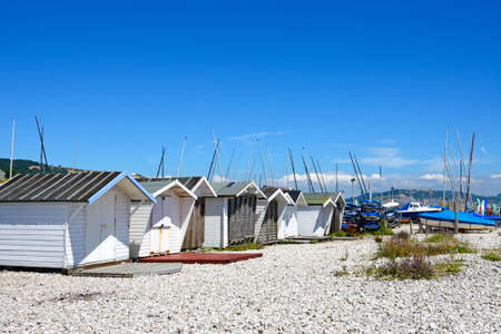 lyme: Huts on the pebbly beach with yachts to the rear, Lyme Regis, Dorset, England, UK, Western Europe.