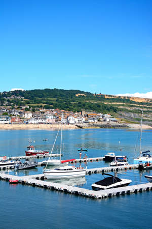 Yachts moored at the pontoon with views towards the Jurassic coastline, Lyme Regis, Dorset, England, UK, Western Europe. Editorial