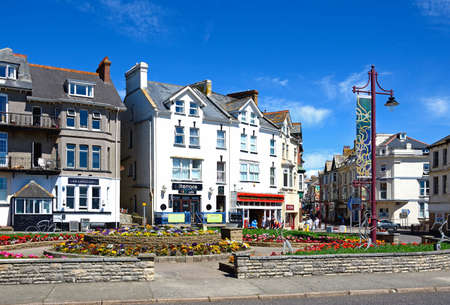 town centre: Pretty flowerbeds on a traffic island with town centre buildings and shops to the rear, Seaton, Devon, England, UK, Western Europe.