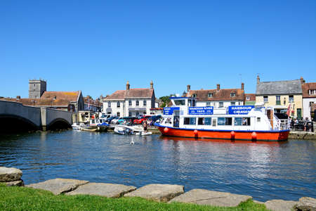 piddle: Boats moored on the river with views towards the bridge and town, Wareham, Dorset, England, UK, Western Europe. Editorial
