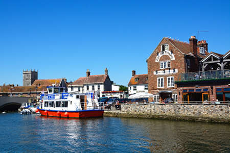 piddle: Boats moored on the river with views towards The Old Granary and church, Wareham, Dorset, England, UK, Western Europe.