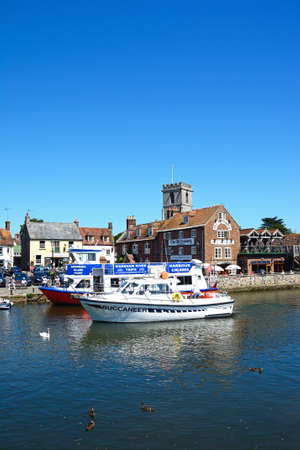 Boats on the river with views towards The Old Granary and Lady St Mary church, Wareham, Dorset, England, UK, Western Europe.