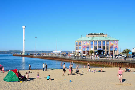 Holidaymakers on the beach with the Pavilion and Jurassic Skyline tower to the rear, Weymouth, Dorset, England, UK, Western Europe. Editorial