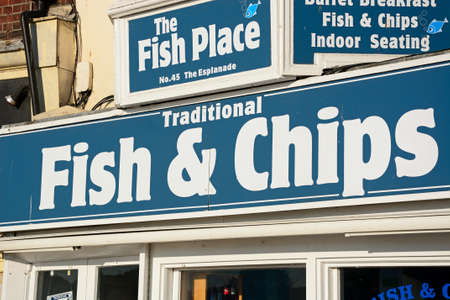 writing western: Traditional fish and chips shop sign along the Esplanade, Weymouth, Dorset, England, UK, Western Europe.