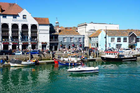 Fishing boats in the harbour with quayside buildings and pubs to the rear, Weymouth, Dorset, England, UK, Western Europe. Editorial