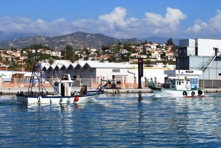 Traditional fishing boats entering the harbour with buildings to the rear, Caleta de Velez, Malaga Province, Andalusia, Spain, Western Europe.