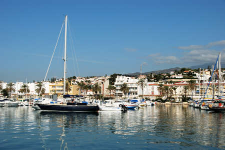 View of yachts moored in the harbour with town buildings to the rear, Caleta de Velez, Malaga Province, Andalusia, Spain, Western Europe.