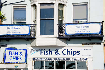 writing western: Traditional fish and chips shop signs along the Esplanade, Weymouth, Dorset, England, UK, Western Europe. Editorial