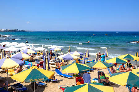 Tourists relaxing on the beach with views towards the sea, Stalida, Crete, Europe.