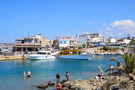 greece shoreline: Tourists on the rocky shoreline with views of boats and restaurants to the rear, Sissi, Crete, Greece, Europe. Editorial