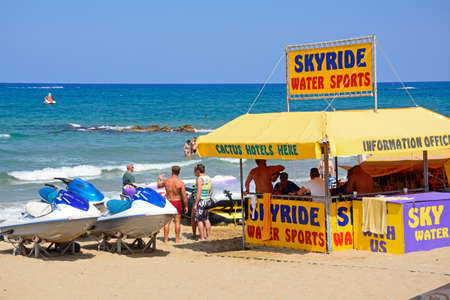 People standing at a water sports tent on the beach, Stalida, Crete, Europe. Editorial