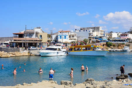 greece shoreline: Tourists in the sea along the rocky shoreline with views of boats and restaurants to the rear, Sissi, Crete, Greece, Europe. Editorial