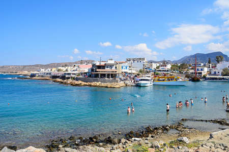 greece shoreline: Tourists in the sea along the rocky shoreline with views of the harbour and town to the rear, Sissi, Crete, Greece, Europe.