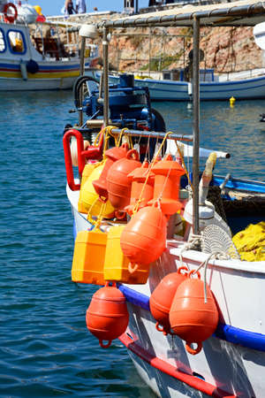 fishing floats: Orange and yellow fishing floats on the back of a Traditional Greek fishing boat moored in the harbour, Sissi, Crete, Greece, Europe.