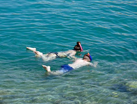 Children snorkelling in shallow water in the bay, Sissi, Crete, Europe.