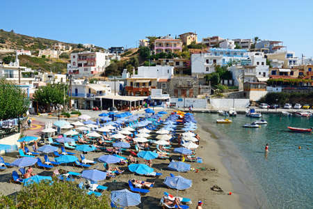 Tourists relaxing on the beach with town buildings to the rear, Bali, Crete, Greece, Europe.