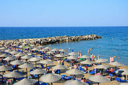 Tourists relaxing on the sandy beach with views towards the breakwater and sea, Panormos, Crete, Greece, Europe.