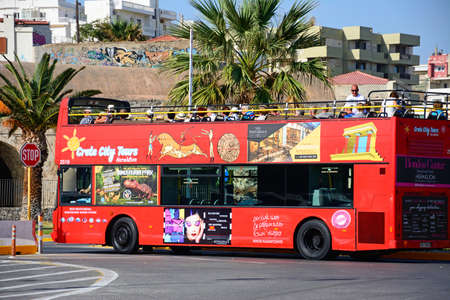 Passengers on a red open topped tour bus parked near the port, Heraklion, Crete, Greece, Europe.