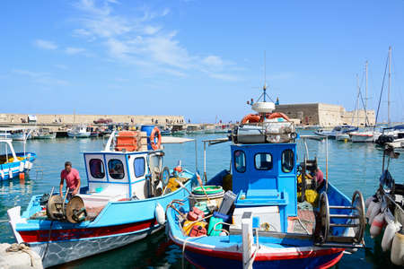 Traditional fishing boats moored in the harbour with Koules castle to the rear, Heraklion, Crete, Greece, Europe. Editorial