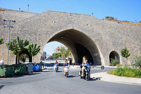 Arch in the city defence wall with people riding mopeds in the foreground, Heraklion, Crete, Greece, Europe.
