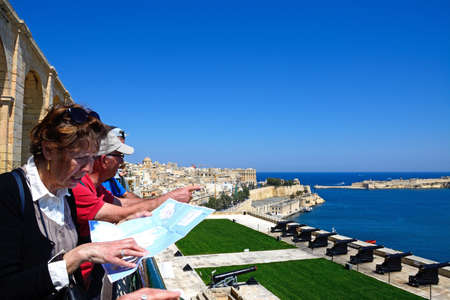 Tourists looking at a map overlooking The Noon Gun in the Saluting Battery seen from the Upper Barrakka Gardens with views over the bay towards Fort Rikasoli, Valletta, Malta, Europe.