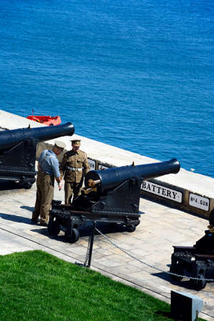 Military personnel preparing The Noon Gun in the Saluting Battery seen from the Upper Barrakka Gardens, Valletta, Malta, Europe.