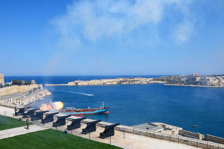 The Noon Gun in the Saluting Battery seen from the Upper Barrakka Gardens with views over the bay towards Fort Rikasoli, Valletta, Malta, Europe.