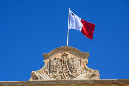 castille: The coat of arms of Castille and Leon and Maltese flag on top of the Auberge de Castille (office of the Prime Minister) in Castille Square, Valletta, Malta, Europe. Stock Photo