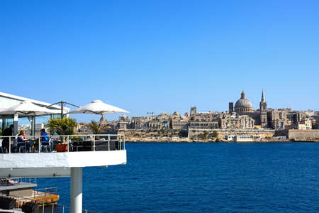 View of St Pauls Anglican Cathedral and the Basilica of Our Lady of Mount Carmel with a cafe in the foreground seen across the Grand Harbour from Sliema, Valletta, Malta, Europe. Editorial
