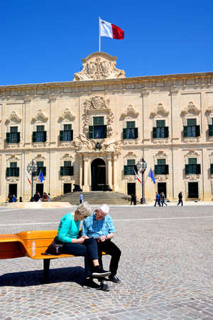 castille: View of the Auberge de Castille in Castille Square with a couple sitting on a bench in the foreground, Valletta, Malta, Europe.