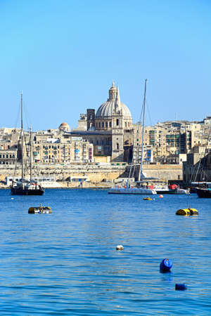 View of St Pauls Anglican Cathedral and the Basilica of Our Lady of Mount Carmel seen from the Grand Harbour, Valletta, Malta, Europe.