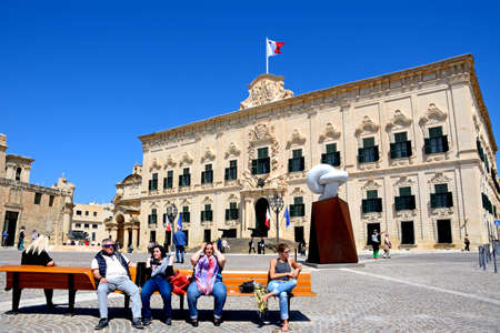 castille: View of the Auberge de Castille in Castille Square with the Bianco Carrara marble sculpture and tourists sitting on a bench in the foreground, Valletta, Malta, Europe.