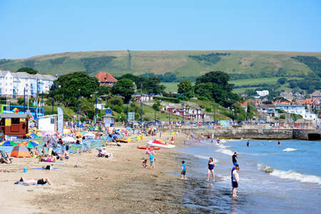 dorset: Holidaymakers on the beach and in the sea with town buildings and harbour wall to the rear, Swanage, Dorset, England, UK, Western Europe. Editorial