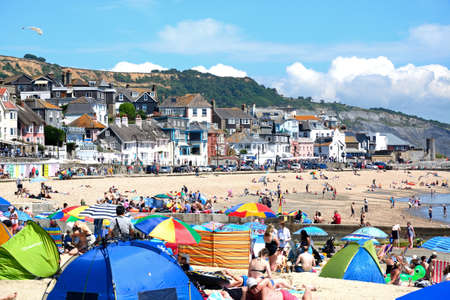 Holidaymakers relaxing on the sandy beach with the promenade to the rear, Lyme Regis, Dorset, England, UK, Western Europe. Editorial