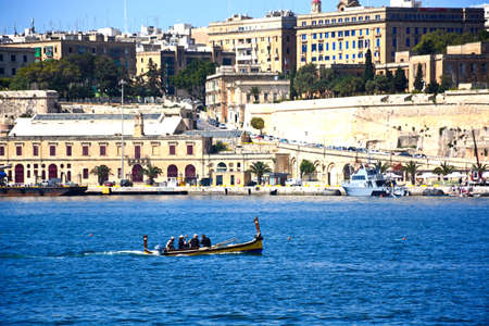 Passengers on board a traditional Maltese Dghajsa water taxi in the grand harbour with views towards Valletta, Vittoriosa, Malta, Europe.