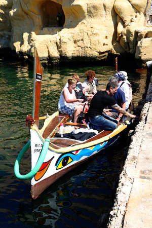 Passengers on board a traditional Maltese Dghajsa water taxi in an inlet alongside Fort San Angelo, Vittoriosa, Malta, Europe. Editorial