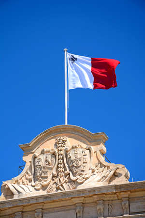 Maltese flag and coast of arms on top of the Auberge de Castille in Castille Square, Valletta, Malta, Europe.