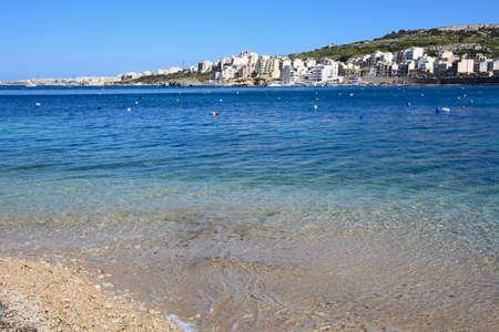 Rocky beach with views across the bay towards St Pauls Bay, San Pawl, Malta, Europe.