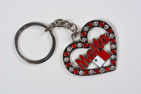 Ruby and diamond encrusted heart shaped Maltese keyring against a white background Stock Photo