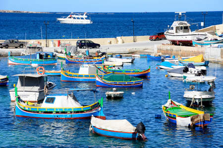 Traditional Maltese Dghajsa fishing boats moored in the harbour with views towards the coastline, San Pawl, Malta, Europe. Editorial