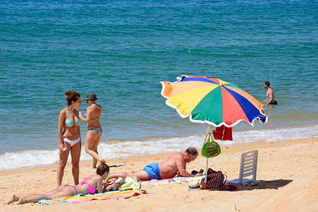 Family relaxing on the waters edge of the beach with views of the Atlantic Ocean, Vilamoura, Algarve, Portugal, Europe.