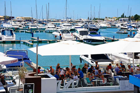 Luxury boats moored in the marina with waterfront restaurants in the foreground, Vilamoura, Algarve, Portugal, Europe.