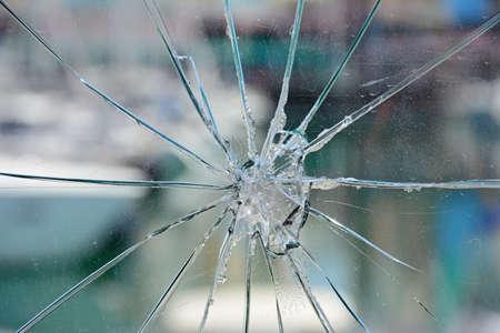 Star burst effect cracks in a glass panel in the marina area, Albufeira, Algarve, Portugal, Europe.