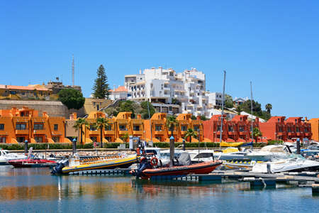 Yachts and motorboats moored in the marina with apartments to the rear, Portimao, Algarve, Portugal, Europe.