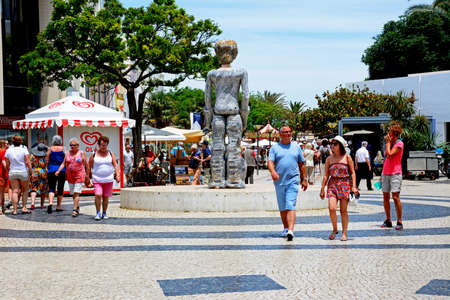 Dom Sebastiao sculpture in the Praca Gil Eanes with tourists enjoying the setting, Lagos, Portugal. Editorial