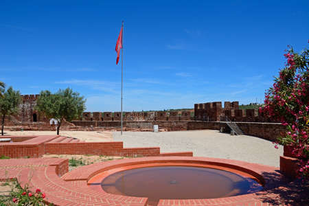 Courtyard and gardens of the Medieval castle with battlements and tower to the rear, Silves, Portugal, Europe.