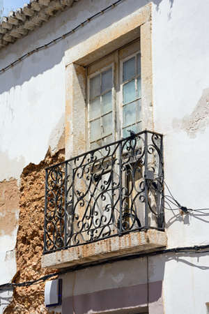 Traditional Portuguese building with a wrought iron balcony in need of restoration along an old town street, Lagos, Algarve, Portugal, Europe.
