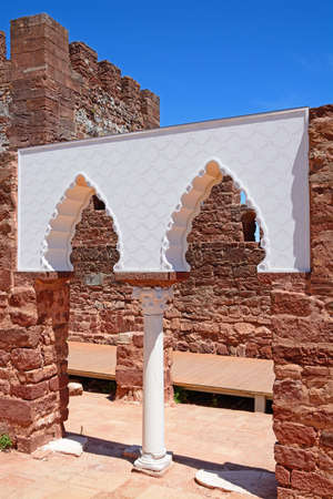 View of the Medieval ruins inside the castle showing the vaulted Moorish windows of the palace of balconies with the battlements and one of the towers to the rear, Silves, Portugal, Europe. Stock Photo