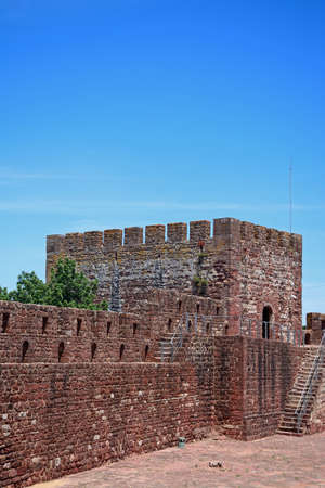 View of part of the Medieval castle battlements and one of the towers, Silves, Portugal, Europe. Stock Photo