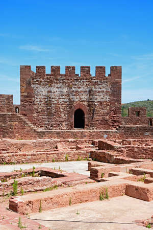 View of the Medieval ruins inside the castle showing with the battlements and one of the towers to the rear, Silves, Portugal, Europe.